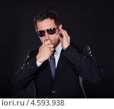 Охранник в темных очках говорит по рации. Стоковое фото, фотограф Андрей Попов / Фотобанк Лори