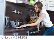 Красивая улыбающаяся девушка проверяет рецепт в интернете на ноутбуке на современной кухне. Стоковое фото, фотограф Okssi / Фотобанк Лори