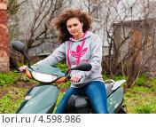 Симпатичная девушка сидит за рулём скутера (2013 год). Редакционное фото, фотограф Игорь Низов / Фотобанк Лори