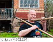 Купить «Мужчина средних лет с лопатой и граблями на плече на фоне дачи», эксклюзивное фото № 4602234, снято 5 мая 2013 г. (c) Игорь Низов / Фотобанк Лори