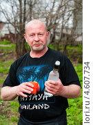 Радостный мужчина с бутылкой водки и стаканом на улице (2013 год). Редакционное фото, фотограф Игорь Низов / Фотобанк Лори