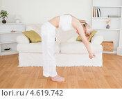 Купить «Блондинка выполняет наклоны, занимаясь дома гимнастикой», фото № 4619742, снято 19 апреля 2011 г. (c) Wavebreak Media / Фотобанк Лори