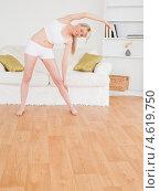 Купить «Блондинка дома занимается гимнастикой, выполняя наклоны в сторону», фото № 4619750, снято 19 апреля 2011 г. (c) Wavebreak Media / Фотобанк Лори