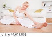 Симпатичная блондинка дома занимается гимнастикой на полу. Стоковое фото, агентство Wavebreak Media / Фотобанк Лори