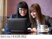 Две девушки смотрят на экран ноутбука в кафе. Стоковое фото, фотограф Александр Жильцов / Фотобанк Лори