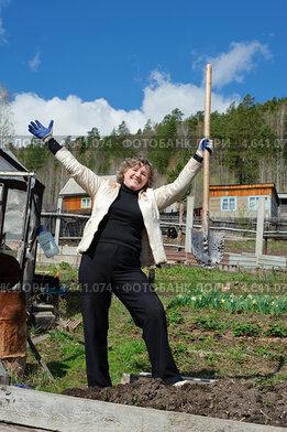 Женщина с лопатой работает в огороде