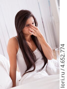 Купить «Молодая женщина с простудой сидит в кровати», фото № 4652774, снято 30 сентября 2012 г. (c) Андрей Попов / Фотобанк Лори