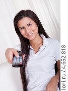 Купить «Улыбающаяся женщина переключает каналы на телевизоре пультом ДУ», фото № 4652818, снято 30 сентября 2012 г. (c) Андрей Попов / Фотобанк Лори