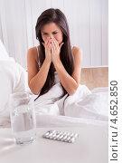 Купить «Молодая женщина с простудой сидит в кровати», фото № 4652850, снято 30 сентября 2012 г. (c) Андрей Попов / Фотобанк Лори