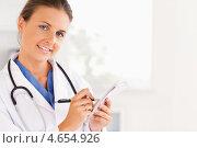 Купить «Женщина-врач позирует на камеру, записывая в историю болезни», фото № 4654926, снято 11 июля 2011 г. (c) Wavebreak Media / Фотобанк Лори