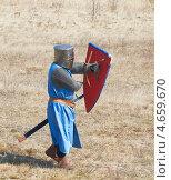 Воин одетый в доспехи средневекового рыцаря с оружием и щитом в руках. Стоковое фото, фотограф Raulin / Фотобанк Лори