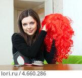 Купить «Молодая женщина держит в руках красный парик», фото № 4660286, снято 21 декабря 2012 г. (c) Яков Филимонов / Фотобанк Лори