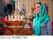 Купить «Девушка ставит свечку в православном храме», фото № 4668114, снято 9 мая 2013 г. (c) Андрей Ярославцев / Фотобанк Лори