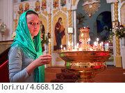 Купить «Девушка ставит свечку в православном храме», фото № 4668126, снято 9 мая 2013 г. (c) Андрей Ярославцев / Фотобанк Лори
