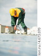 Купить «Кровельщик работает на крыше строящегося здания», фото № 4673070, снято 26 апреля 2012 г. (c) Дмитрий Калиновский / Фотобанк Лори