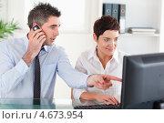 Купить «Коллеги работают на компьютере. Мужчина говорит по мобильному телефону», фото № 4673954, снято 3 августа 2011 г. (c) Wavebreak Media / Фотобанк Лори