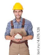 Веселый строитель в каске держит в руках модель дома. Стоковое фото, фотограф Андрей Попов / Фотобанк Лори