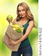 Купить «Девушка держит в руках бумажный пакет с фруктами», фото № 4676622, снято 8 декабря 2012 г. (c) Syda Productions / Фотобанк Лори