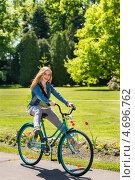 Купить «Молодая девушка катается на велосипеде в парке», фото № 4696762, снято 15 мая 2013 г. (c) CandyBox Images / Фотобанк Лори