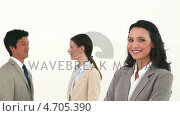 Купить «Young businesswoman posing while her colleagues are talking», видеоролик № 4705390, снято 18 июня 2019 г. (c) Wavebreak Media / Фотобанк Лори