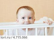 Купить «Ребенок (8 месяцев) грызет кроватку», фото № 4715066, снято 4 июня 2013 г. (c) ivolodina / Фотобанк Лори