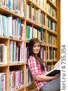 Купить «Молодая студентка сидит, читая книгу, в библиотеке на полу», фото № 4735354, снято 1 сентября 2011 г. (c) Wavebreak Media / Фотобанк Лори