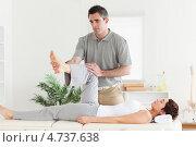 Купить «Девушке на массажном столе делают массаж полусогнутой ноги», фото № 4737638, снято 11 августа 2011 г. (c) Wavebreak Media / Фотобанк Лори