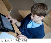 Школьник работает на планшетном компьютере в классе. Стоковое фото, фотограф Римма Зайцева / Фотобанк Лори