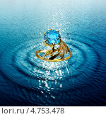 Купить «Золотое кольцо с синим камнем на фоне воды», фото № 4753478, снято 16 октября 2018 г. (c) ElenArt / Фотобанк Лори