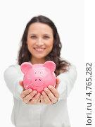 Купить «Девушка держит перед собой в руках копилку-свинью», фото № 4765282, снято 21 ноября 2011 г. (c) Wavebreak Media / Фотобанк Лори