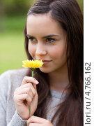 Купить «Молодая женщина улыбается, смотря в сторону и вдыхая аромат цветка», фото № 4766162, снято 14 ноября 2011 г. (c) Wavebreak Media / Фотобанк Лори