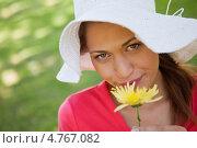 Купить «Девушка в шляпе улыбается и держит в руке цветок», фото № 4767082, снято 16 ноября 2011 г. (c) Wavebreak Media / Фотобанк Лори