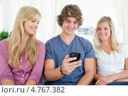 Купить «Улыбающийся парень держит в руке телефон сидя в окружении молодых девушек», фото № 4767382, снято 23 ноября 2011 г. (c) Wavebreak Media / Фотобанк Лори