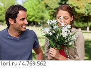 Купить «Красивая молодая женщина вдыхает аромат цветов, а мужчина смотрит на нее», фото № 4769562, снято 16 ноября 2011 г. (c) Wavebreak Media / Фотобанк Лори