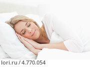 Молодая женщина спит на кровати, укрывшись одеялом и подложив руки под голову. Стоковое фото, агентство Wavebreak Media / Фотобанк Лори