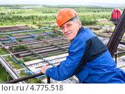 Пожилой мужчина в строительной каске на фоне промышленного пейзажа. Стоковое фото, фотограф Кекяляйнен Андрей / Фотобанк Лори