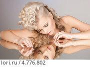 Купить «Красивая девушка с волнистыми светлыми волосами смотрит на свое отражение в зеркале», фото № 4776802, снято 20 февраля 2010 г. (c) Syda Productions / Фотобанк Лори