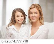 Купить «Счастливая девочка сидит рядышком с мамой на диване», фото № 4777718, снято 20 января 2013 г. (c) Syda Productions / Фотобанк Лори