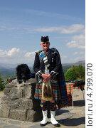 Шотландец в килте на фоне озера Гарри в Шотландии (2013 год). Редакционное фото, фотограф Natalya Sidorova / Фотобанк Лори