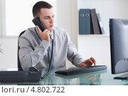 Купить «Бизнесмен слушает звонящего и печатает», фото № 4802722, снято 21 сентября 2011 г. (c) Wavebreak Media / Фотобанк Лори