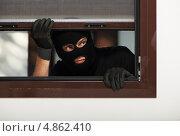 Купить «Вор домушник проникает в чужую квартиру через окно», фото № 4862410, снято 20 июня 2013 г. (c) Дмитрий Калиновский / Фотобанк Лори