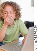 Изображение зевающего мальчика, пользующегося компьютером. Стоковое фото, агентство Wavebreak Media / Фотобанк Лори