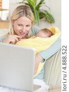 Мама в гостинной со своим малышом смотрит в компьютер. Стоковое фото, агентство Wavebreak Media / Фотобанк Лори