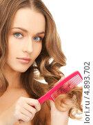 Купить «Красивая молодая женщина с красной пластиковой расческой», фото № 4893702, снято 10 октября 2010 г. (c) Syda Productions / Фотобанк Лори