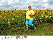 Купить «Толстая женщина бежит мимо подсолнухов», фото № 4896870, снято 14 июля 2013 г. (c) Михаил Коханчиков / Фотобанк Лори