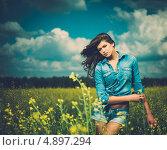 Купить «Красивая молодая брюнетка в шортах и джинсовой рубашке на цветущем поле», фото № 4897294, снято 26 июня 2013 г. (c) Andrejs Pidjass / Фотобанк Лори