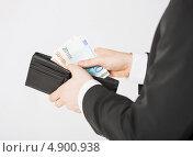 Купить «Бизнесмен в костюме убирает деньги», фото № 4900938, снято 21 марта 2013 г. (c) Syda Productions / Фотобанк Лори
