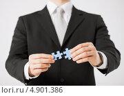 Купить «Мужчина соединяет два элемента пазла», фото № 4901386, снято 21 марта 2013 г. (c) Syda Productions / Фотобанк Лори