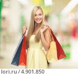 Купить «Счастливая девушка в желтом платье с покупками в пакетах в магазине», фото № 4901850, снято 30 марта 2013 г. (c) Syda Productions / Фотобанк Лори