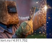 Купить «Электросварщик в защитной маске сваривает металлоконструкцию», фото № 4911702, снято 21 июля 2013 г. (c) Илья Андриянов / Фотобанк Лори